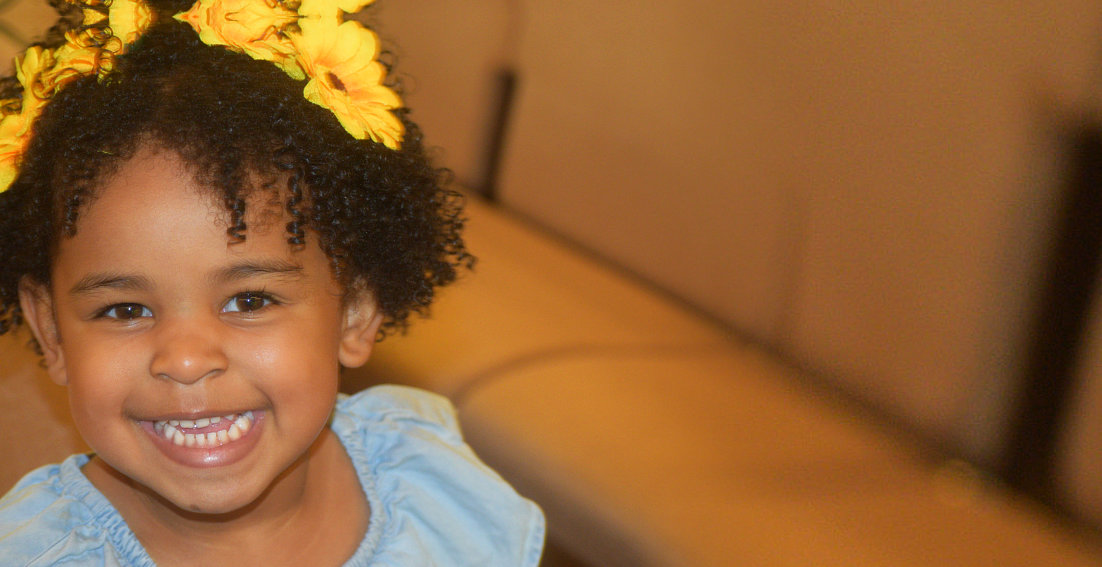 girl with yellow flower on head smiling