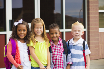 four pre-kindergarten students smiling while standing